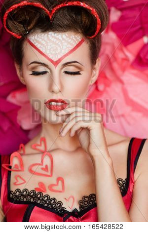 Attractive lady with valentine day makeup and heart decoration touching her lips with closed eyes. Satisfaction, sensuality, sex, love concept