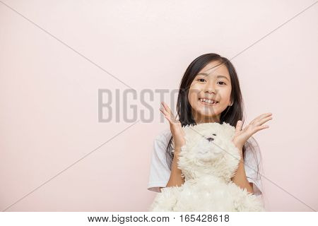 Child Little Girl Asian Thai Nationality With White Toy Teddy Bear Over Pink Wall Background Smiley.