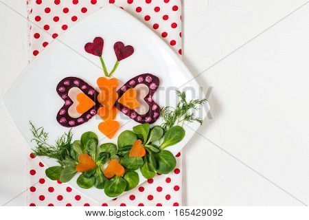 Creative idea of food decoration for Valentines Day. Bright butterfly carved heart-shaped beetroot cheese carrots on a glade of corn salad. Healthy and vegetarian food. Symbols of Valentines Day