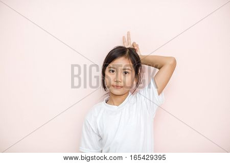 Asian Tanned Skin Girl Child Portrait Over Pink Wall Background Shows Two Fingers On Her Head.