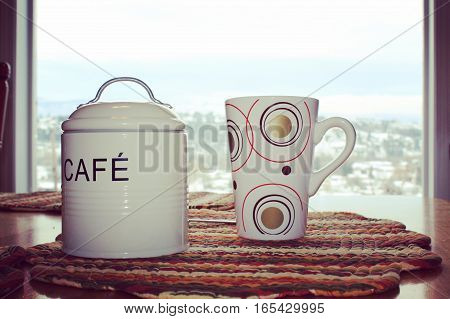 Close up of mug,spoon and tin coffee canister with lid and handle on colorful place mat on wooden table. Scenic winter landscape of snow covered hills and blue sky white clouds in background.