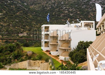 Modern Greek architecture new white building in constructivist style stands on shore of Cretan sea. On flagpole flag of Greece. Resort village Bali Rethymno Crete Greece