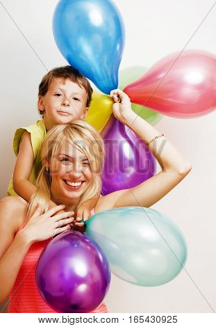 pretty family with color balloons on white background, blond woman with little boy at birthday party