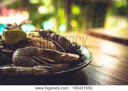 Marinated seafood of tiger prawns for barbecue on black plate on wooden table during seafood cooking