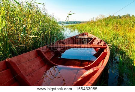 Old red wooden fishing boat at the lake in summer sunny day