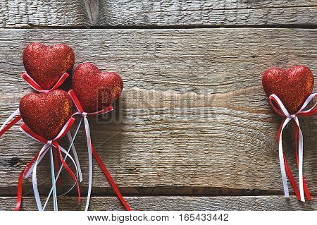 Valentines day. Red hearts on wooden background closeup with copy space for congratulation. Vintage toning