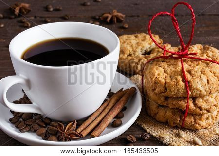 coffee cup with spices and oat cookies tied with heart shaped red ribbon on wooden background. close up. valentines day concept