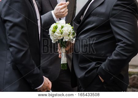 Groom style. Suit with wedding bouquet. Big wedding day