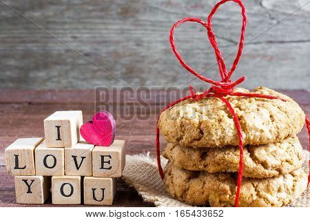 i love you inscription and homemade oat cookies tied with heart shaped red ribbon on wooden table. valentines day concept