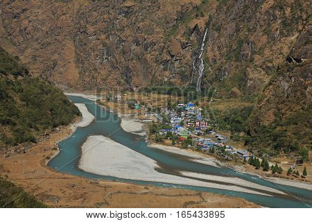 Scene in the Annapurna Conservation Area Nepal. Turquoise Marsyangdi river. Colorful houses of Tal. Waterfall.