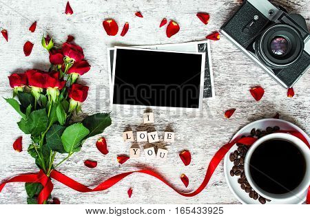coffee cup vintage retro camera with photo frame to placed your picture red roses with petals and i love you inscription. top view. valentines day background