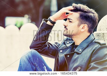 Worried young man with stylish hair cut. Outdoors sitting.