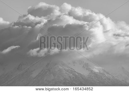 White fluffy clouds cover the top of snowy mountains.