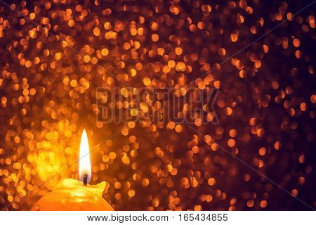 Festive background with glowing candle sparkles and bokeh in warm colors