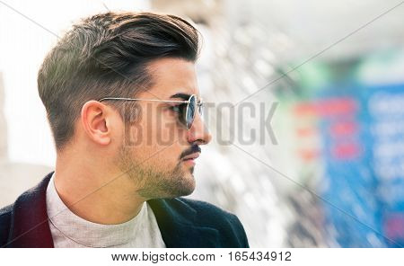 Stylish straight hair. Handsome man profile with sunglasses. Outdoors.