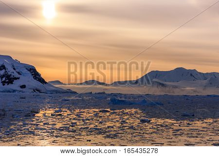 Sunset Over The Mountains And Icebergs At Lemaire Strait, Antarctica