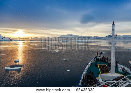 Sunset view and people gathered on the deck Icebergs drifting at Lemaire Channel Antarctica