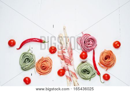 Colorful rolled pasta, cherry tomatoes and bacon on the white wooden background. Top view