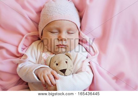 Cute newborn baby in hat sleeps with a toy teddy bear white