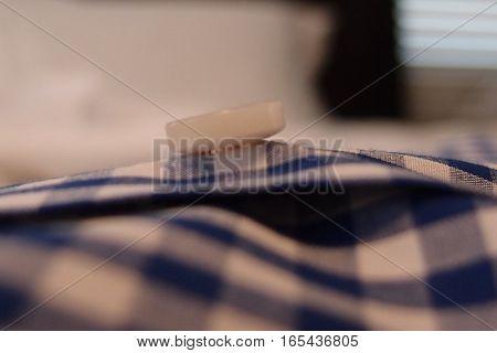 A close-up of a button on a blue gingham check men's dress shirt.