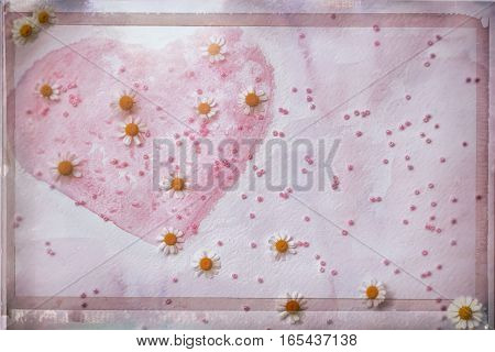 Valentine's Day concept, pink abstract hand-drawn watercolor heart, decorated with beads and fresh chamomile. Space for the text.
