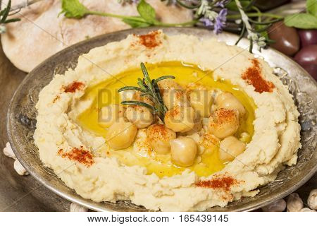 Hummus with herbs in a vintage bowl