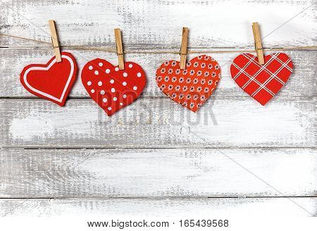 handmade toy hearts hanging from a rope on a white wooden background. Valentine day background with copy space.