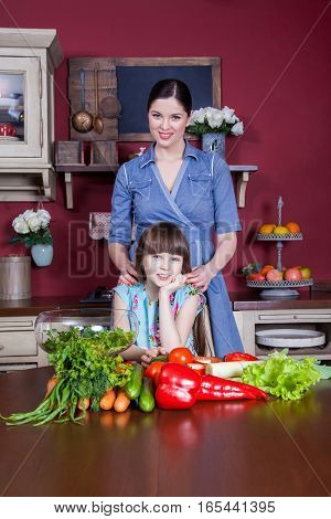 Happy mother and daughter enjoy making and having healthy meal together at their kitchen. they are making vegetable salad and having fun together. mom take care of her daughter and tech how to cook.