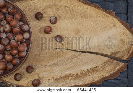 Hazelnut in shell on a brown wooden surface top view an empty space on the right