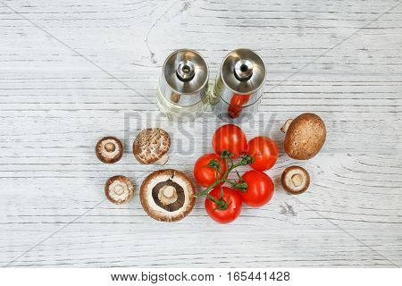 Mushrooms tomatoes olive oil and vinegar on a wooden table