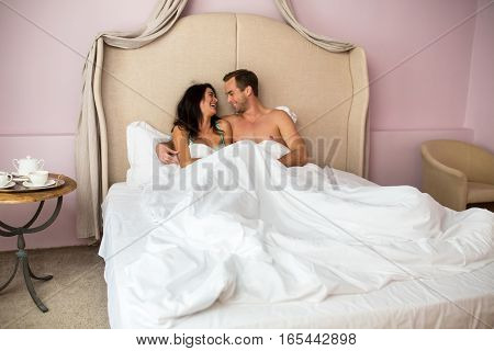 Couple in bed smiling. Happy woman and man. Mood and romance.
