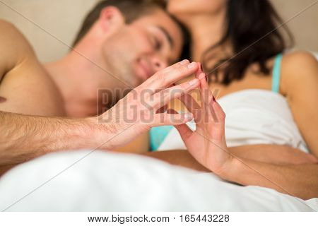 Couple in bed touching hands. Young caucasian man and woman. Tenderness of every touch.