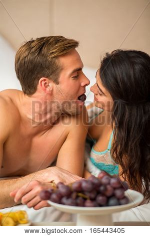 Couple eating grapes in bedroom. Woman and man lying. Health and love.