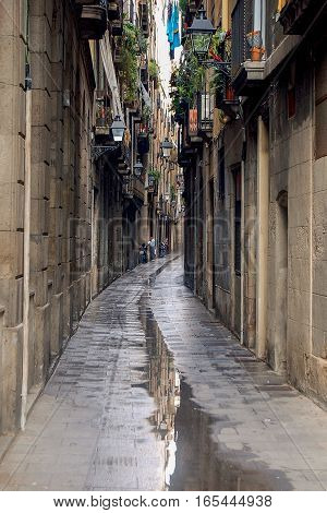 Puddle after rain in a narrow alley of the Barri Quarter of Barcelona in Catalonia, Spain