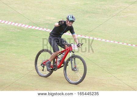 Happy Middle Aged Man Riding To The Finish Line At Mountain Bike Race