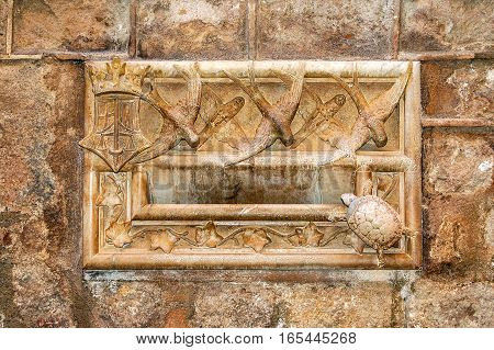 Stone letterbox with carved birds, turtle and leaves of the Casa Ardiaca in Barcelona, Catalonia, Spain