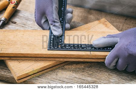 Carpenter Measuring With A Metal Angle