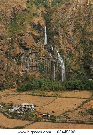 Tall waterfall in Tal Annapurna Conservation Area Nepal. Trekking trail and hotel.