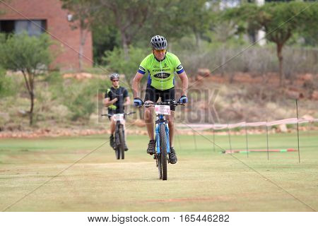 Middle Aged Man Chasing To The Finish Line At Mountain Bike Race