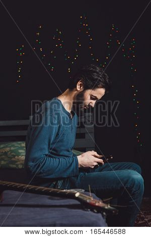 Tensed man using mobile phone, sitting on bed