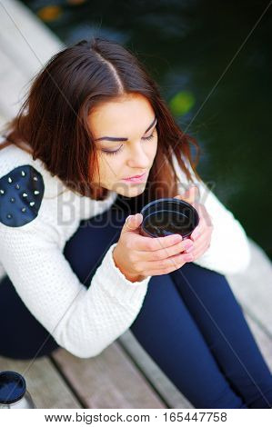 brunette girl sitting with a cup of tea from a thermos