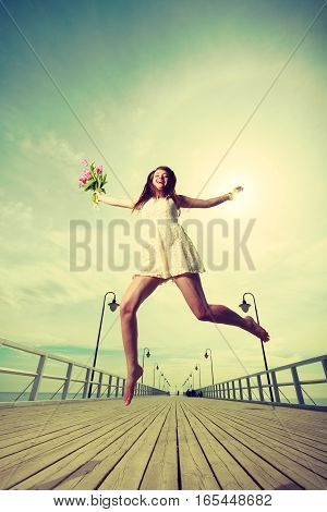 Happiness romance success concept. Woman wearing short white dress jumping on pier holding bouquet of flowers.