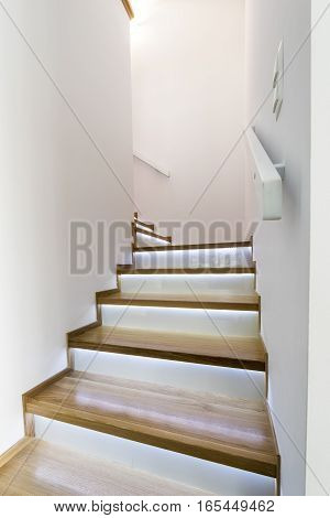 Modern wooden staircase with glass finishing .