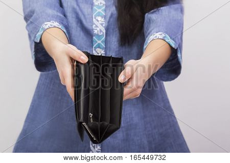 empty purse in women's hands on a light background