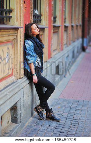 Young slim long haired brunette girl in stylish clothes youth standing thoughtfully leaning against the wall of an old St. Petersburg building.