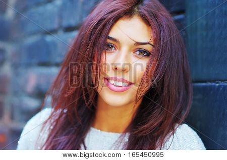 Portrait of young beautiful smiling girl with a great makeup posing against a brick wall on a summer day closeup.
