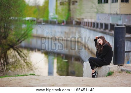portrait of a dreamy beautiful long-haired brunette woman sitting on the street near the concrete barriers of channel on blurred background of a city street.