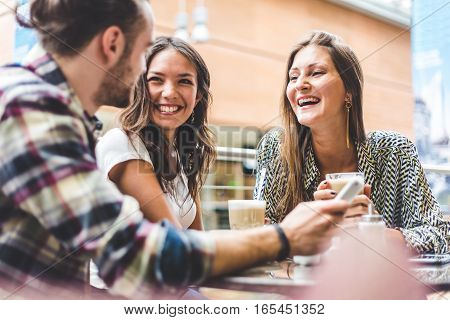 Multiracial group of friends having a coffee together. Two women and a man at cafe talking laughing and enjoying their time. Lifestyle and friendship concepts with real people models.