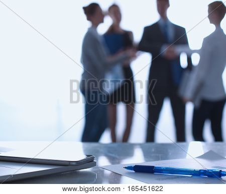 Laptop  computer on the desk , businesspeople standing in the background.
