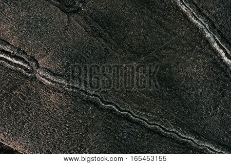 Background of brown sheepskin with rough structure seams. Macro view
